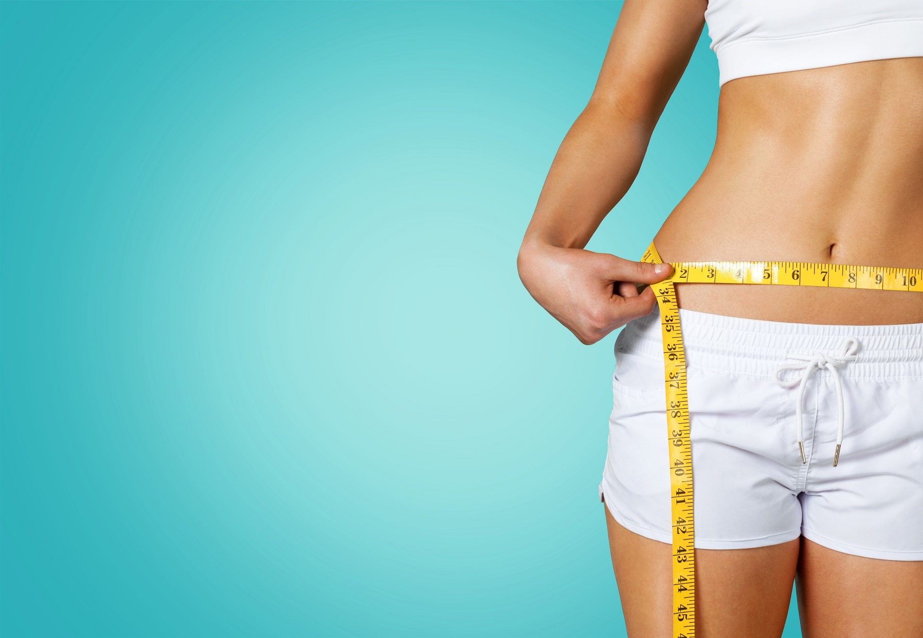 Slim young woman measuring her thin waist